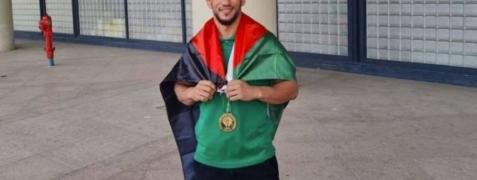 البطل الجزائري متوشحًا بالعلم الفلسطيتي